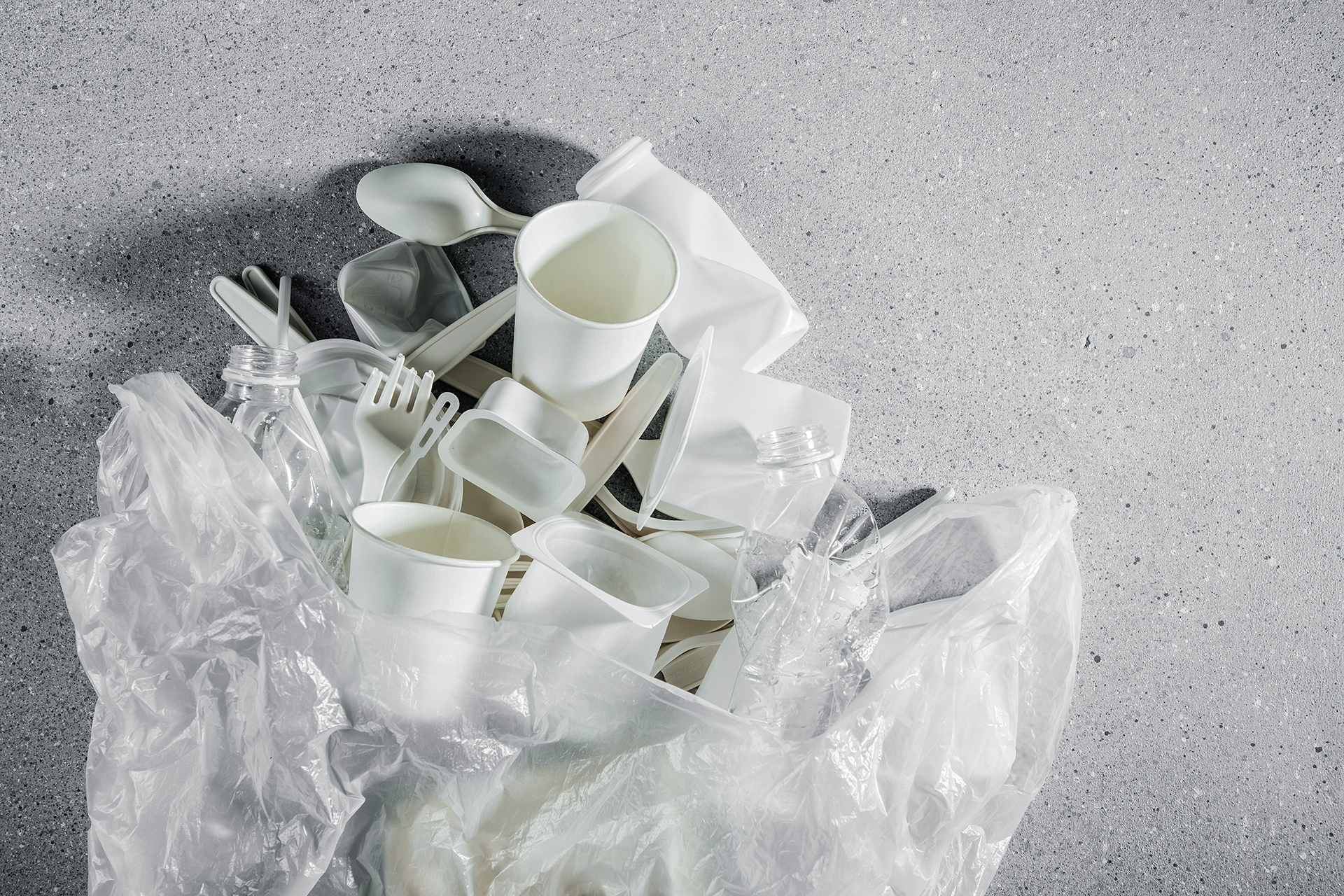 Different kinds of plastic garbage in plastic bag. Food plastic packaging on light background. Concept of Recycling plastic and ecology. Flat lay, top view